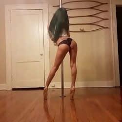 Modelo negra en lencería y tacones bailando pole dance